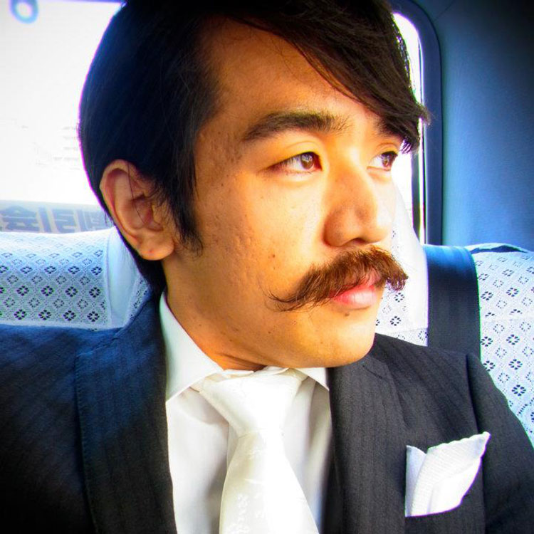 asian man with mustache in the back of a car
