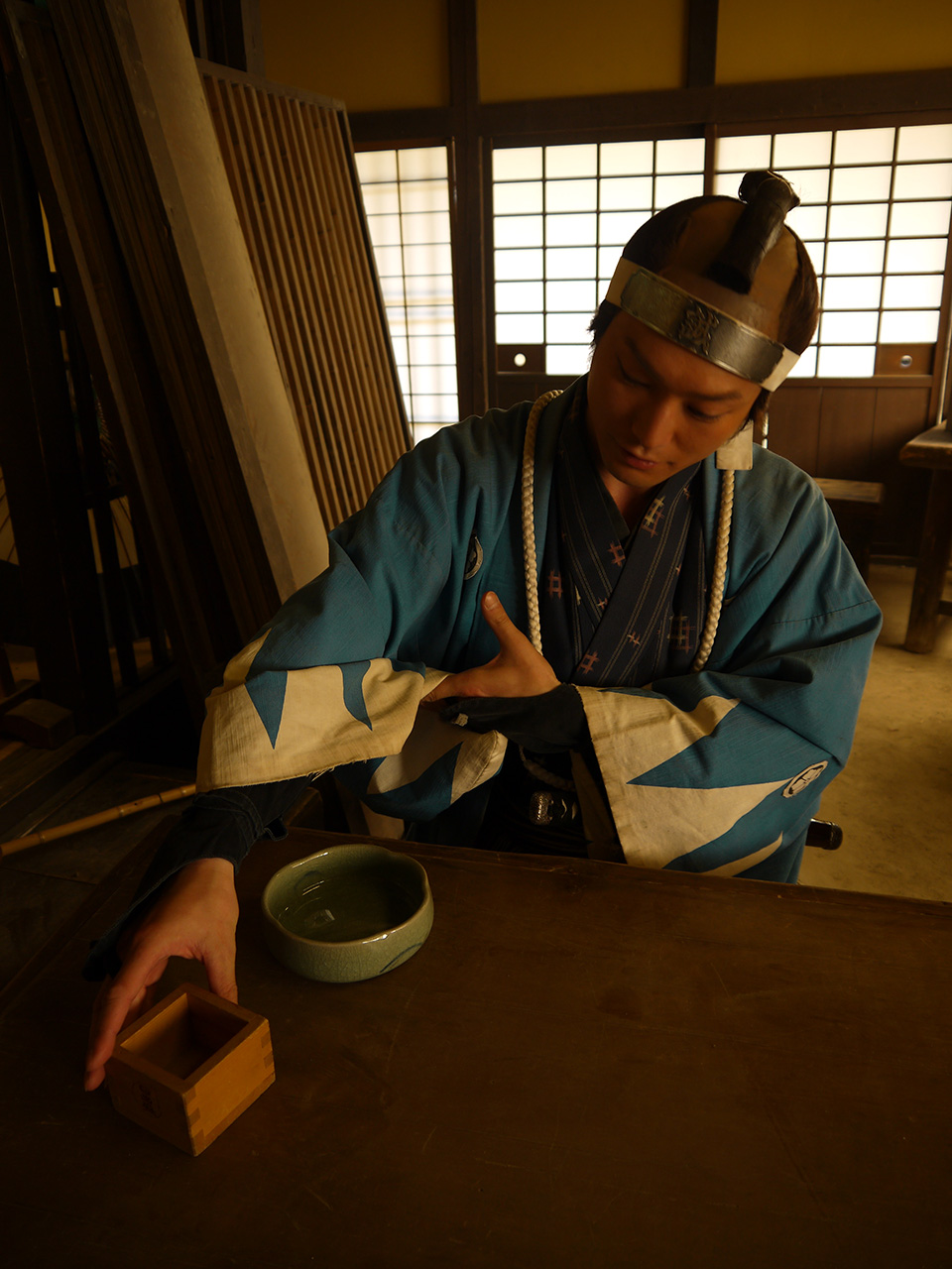 Takahiro Hotta in blue hakama reaching for cup tamoto