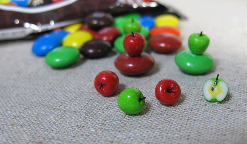 Miniature apples on top of M&Ms