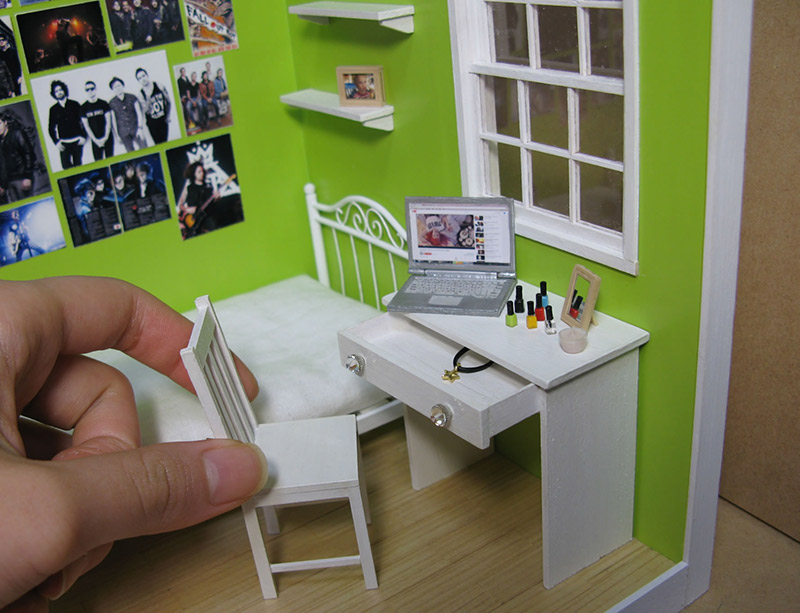 A normal-sized hand pulling out a chair from a small desk in a miniature room