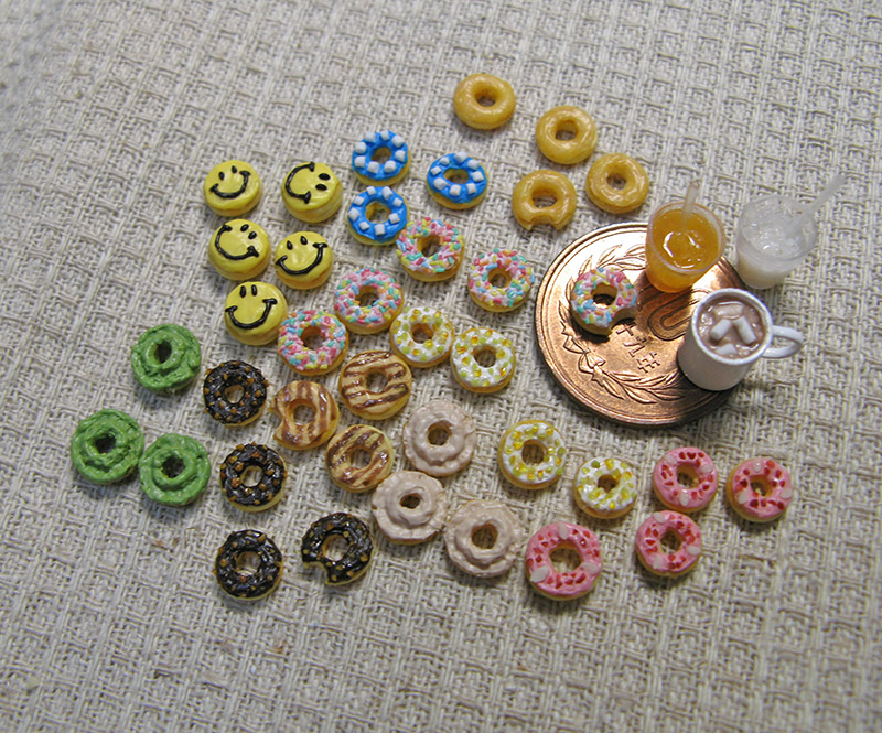 A group of miniature donuts and a 10 yen coin. About 6 mini donuts could fit on the coin.