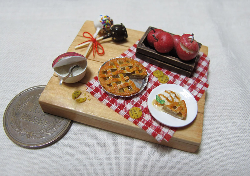 A miniature apple pie set next to a 10 yen coin. The pie is about 25 percent smaller
