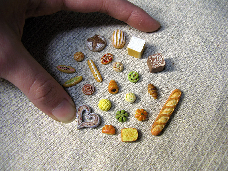 A group of miniature bread encircled by a normal-sized hand