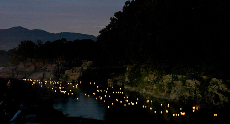 Obon lanterns float down a river