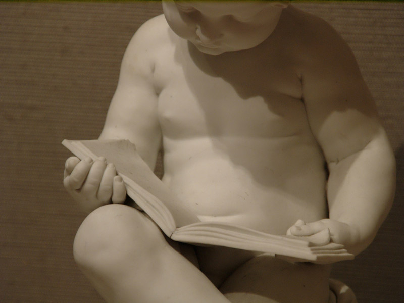 ceramic baby statue reading a book