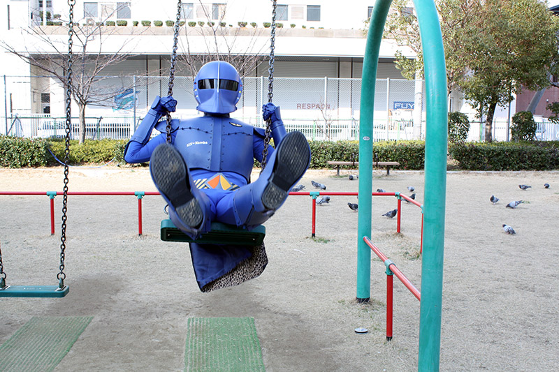 Rapi:tldier the Japanese superhero swings on a swing set
