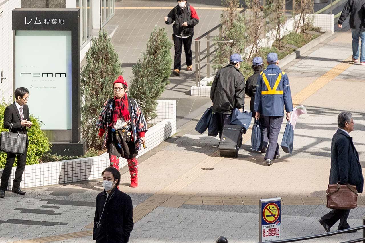 Homeless rental Kotani waiting at the crosswalk in Akihabara Japan