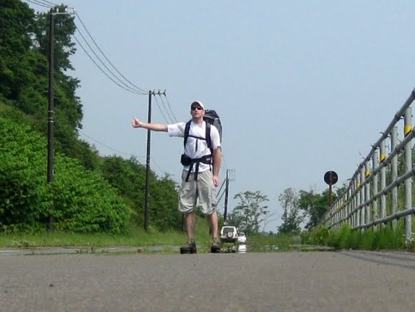 a man standing in the road hitchhiking in japan