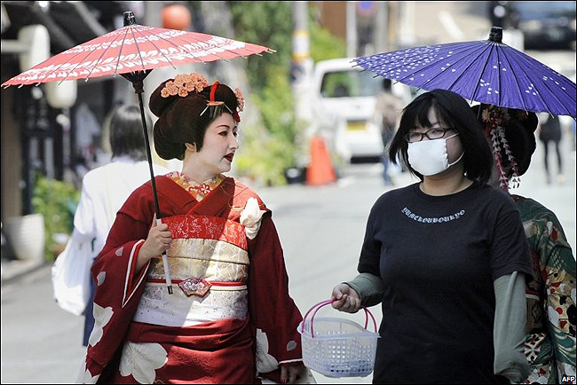 Japanese woman in a surgical mask walking with two geishas