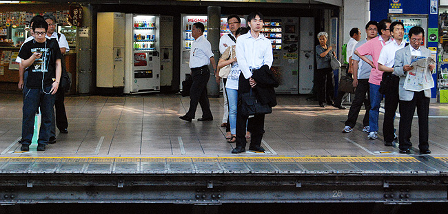 Japanese men standing in line at a train station