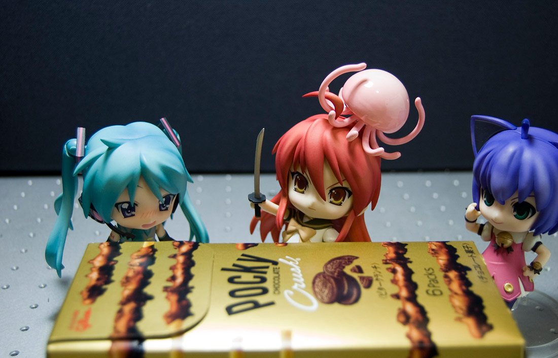 small anime figures surrounding a box of pocky