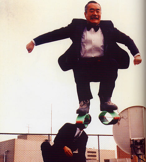 Dr. NakaMats jumping into the air with spring-like contraptions stuck to his feet