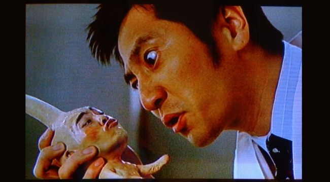 a japanese man staring at a baby creature