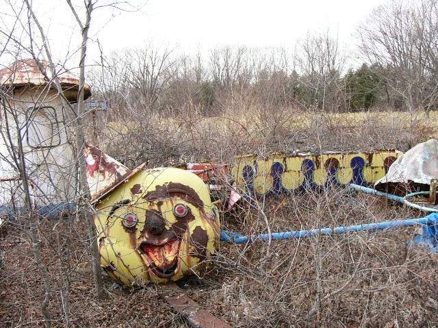 A rusty clown train at an abandoned Japanese amusement park