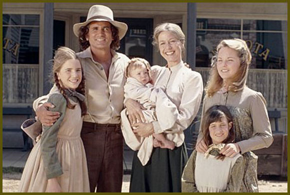 Screenshot from Little House on the Prarie with the main characters standing for a family photo