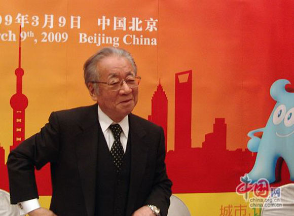 A Japanese man in a suit with glasses against a stylized Beijing skyline background