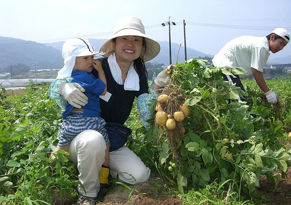 a woman holding a child at a wwoof japan farm