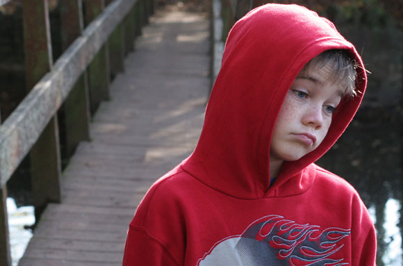 A despondent child in a red hoodie