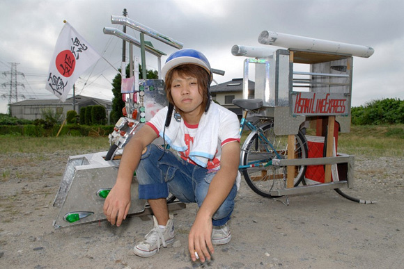Japanese boy kneeling in front of his dekochari bicycle