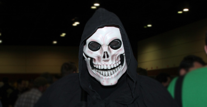 A man in a black hoodie wearing a skull mask