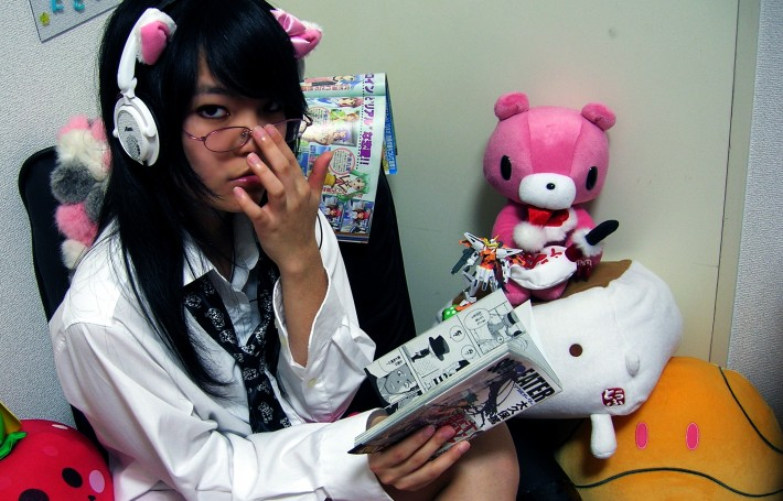 stereotypical otaku in japan reading manga surrounded by stuffed anime toys