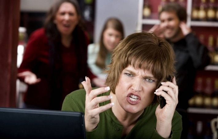 Stock image of a woman speaking angrily on the phone with irritated people behind her