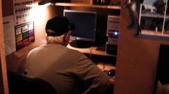 Man in a small cubicle in front of a computer