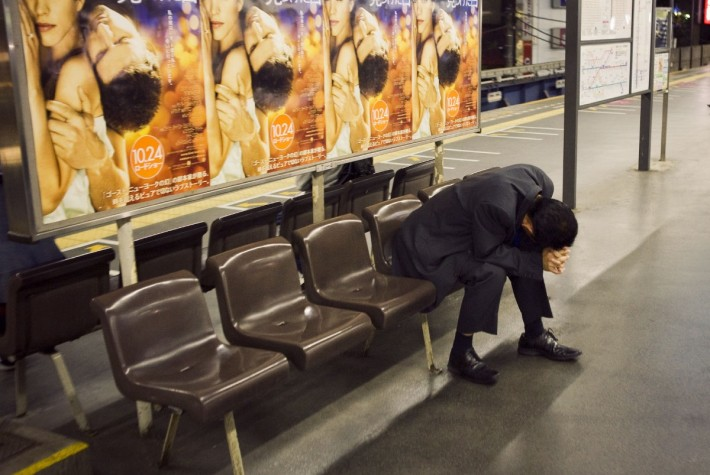 Man with his head in his hands on the benches at a train station