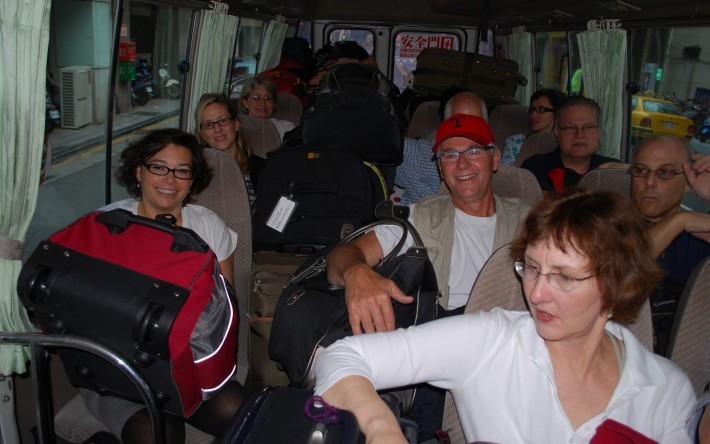 Tourists on a bus with bulky luggage on their laps and other seats