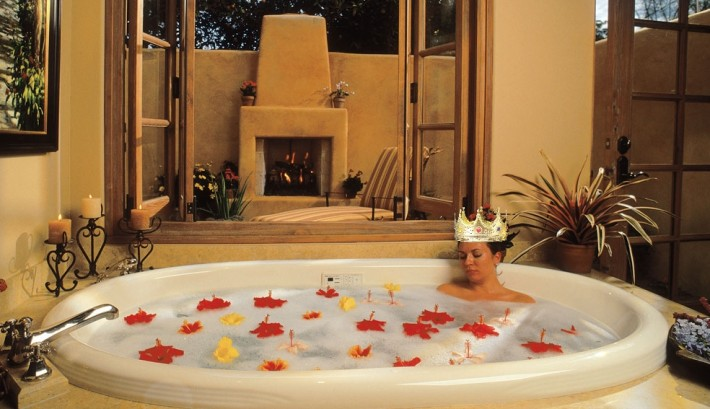 Woman with a crown in a bathtub filled with flowers