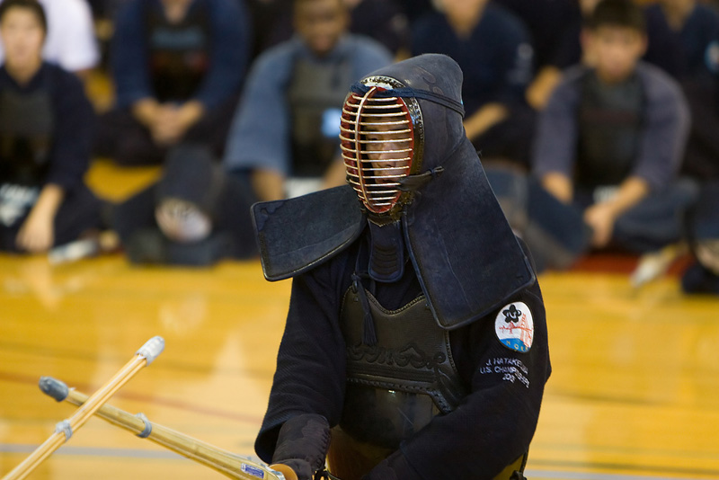 single kendo player in front of a crowd watching