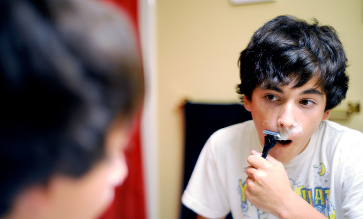 young boy with brown hair trying to shave