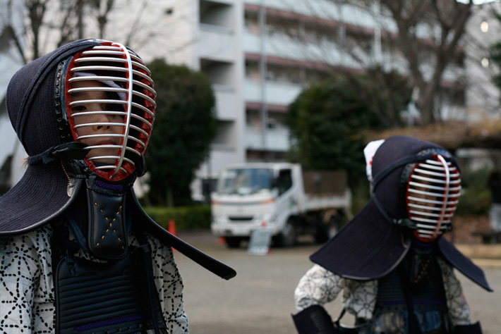 two people shoulders up kendo helmets and uniforms