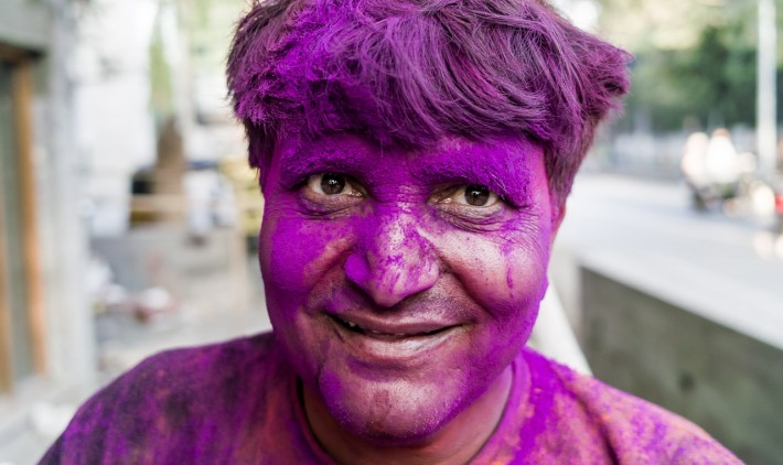 A man covered in purple powder