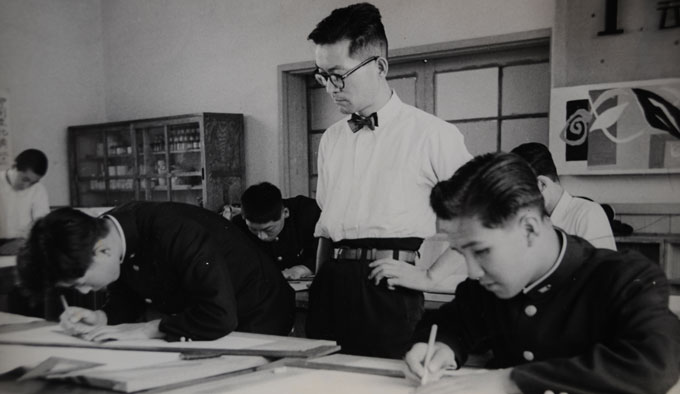 High school teacher sternly looks over his students studying