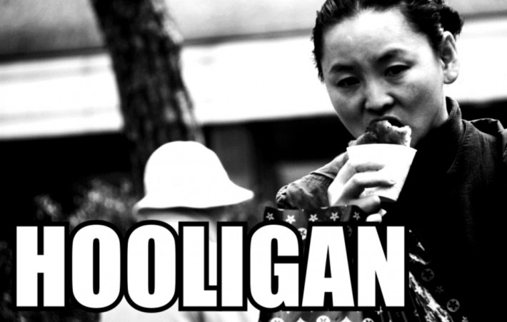 Meme of woman walking while eating with the text Hooligan