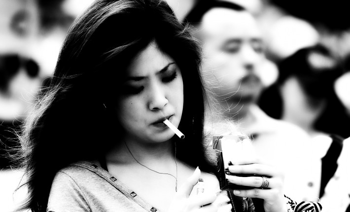 Japanese woman walking while smoking a cigarette