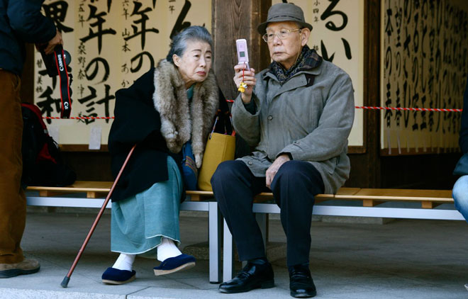 Elderly couple sit on a bench and use their cellphone