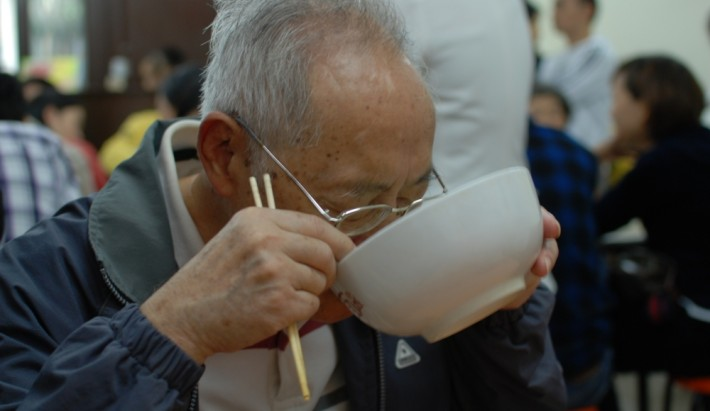An elderly Japanese man lifting up his bowl of noodles