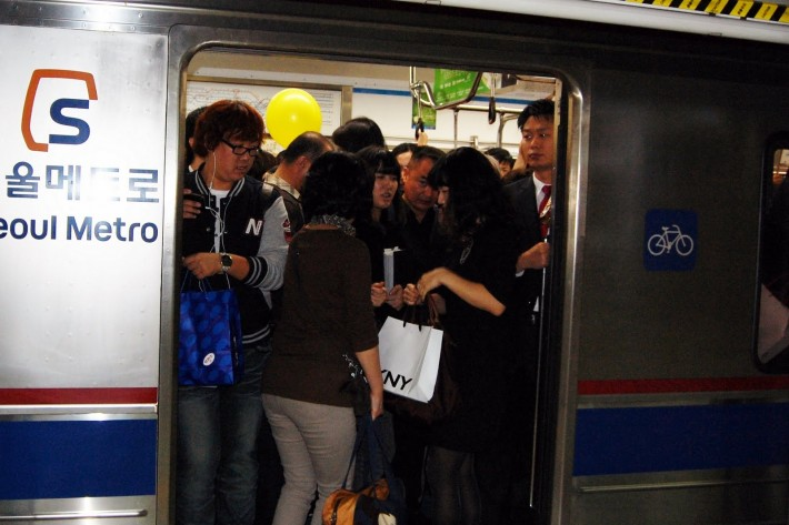Passengers entering a packed subway car at rush hour