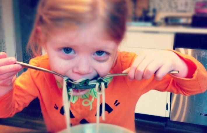 A toddler slurping her noodles