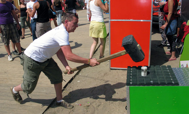 Man at a carnival bringing a large hammer down on a peg