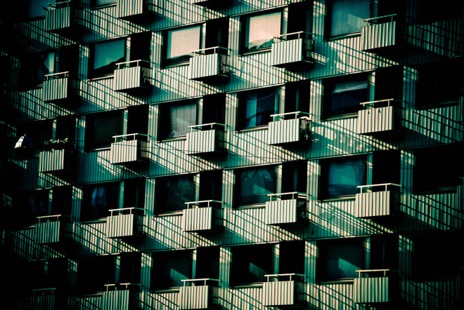A heavily-filtered photograph of a Japanese apartment building from the outside where all the units look exactly the same