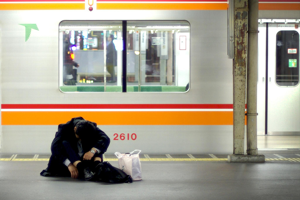 sleepy salaryman waiting for the train