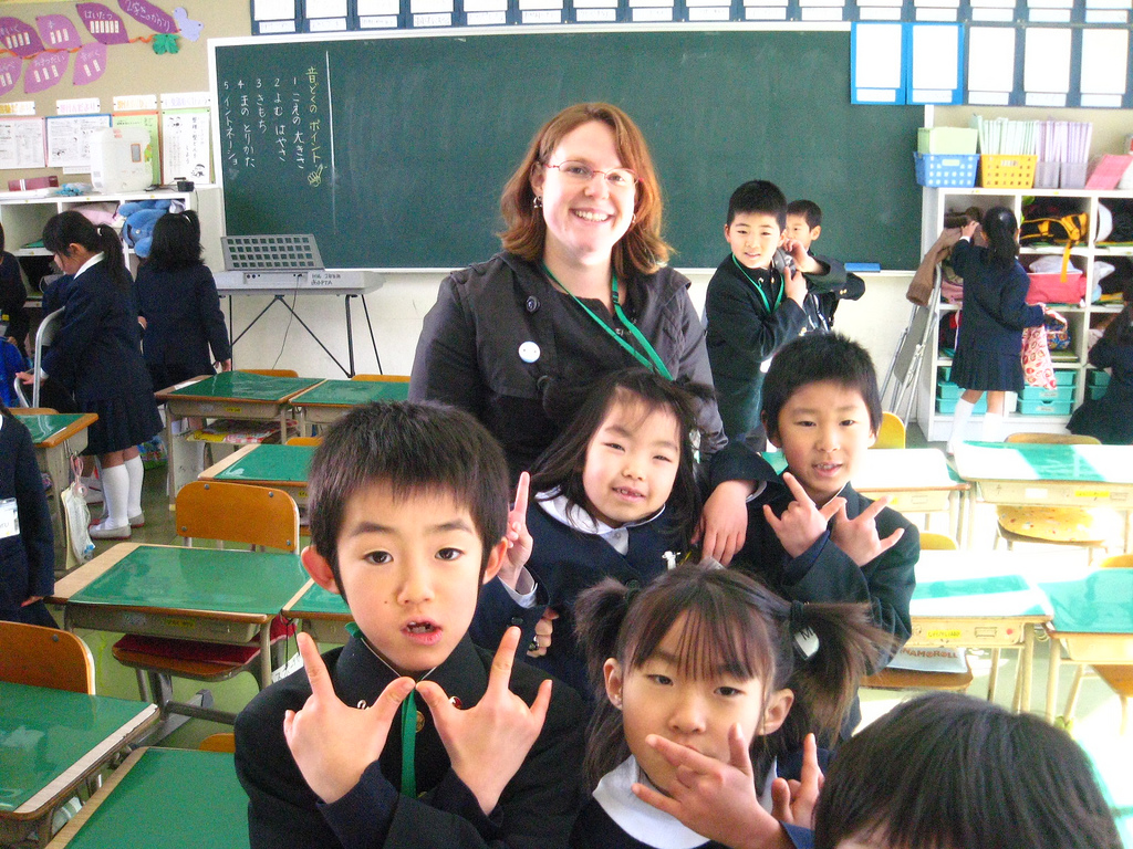 teacher posing with japanese students