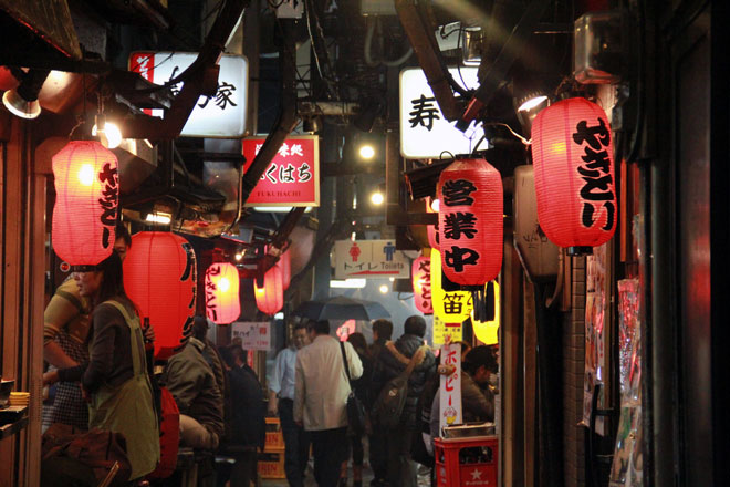japanese piss alley in tokyo with red lanterns and wandering people