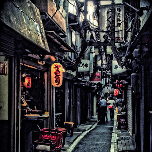 two people walking through piss alley in tokyo japan