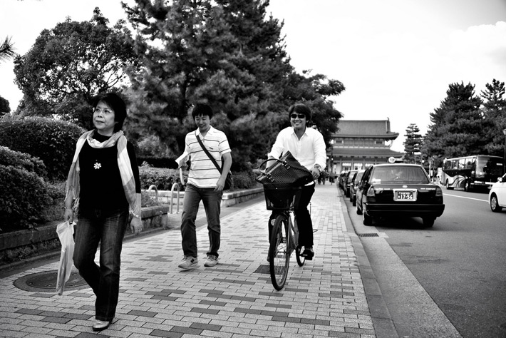 biking down the street in japan around pedestrians