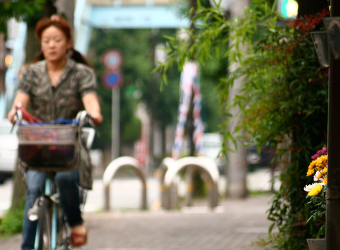 japanese woman riding a bicycle down the street