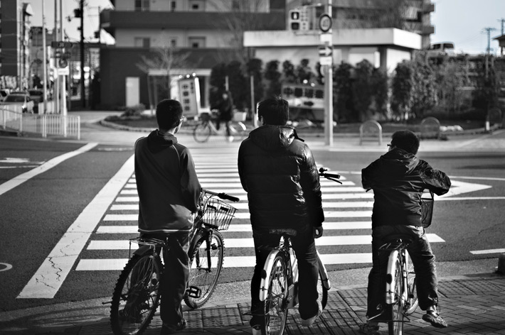 three kids on bicycles waiting to cross the street
